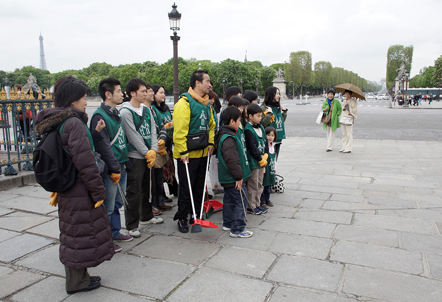 FILE PHOTO: Japanese volunteers pose for a group photo at Place de la Concorde in Paris, as Japanese tourists (R) watch, on April 19, 2009 © Thomas White