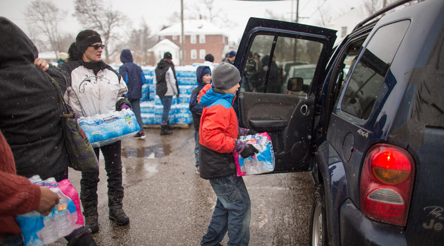 Volunteers load cases of free water into waiting vehicles at a water distribution centre at Salem Lutheran Church in Flint, Michigan, on March 5, 2016. © Geoff Robins