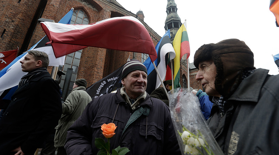 People hold flowers as they wait for an annual procession commemorating the Latvian Waffen-SS (Schutzstaffel) unit, also known as the Legionnaires, in Riga, Latvia, March 16, 2016 © Ints Kalnins