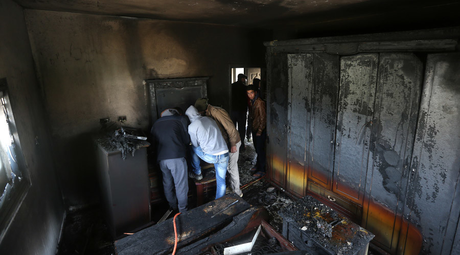 Palestinians inspect the damage inside a burnt-out house belonging to a key witness to an arson attack which took place last year by Jewish extremists that killed a Palestinian family, in the Israeli occupied West Bank village of Duma © JAAFAR ASHTIYEH