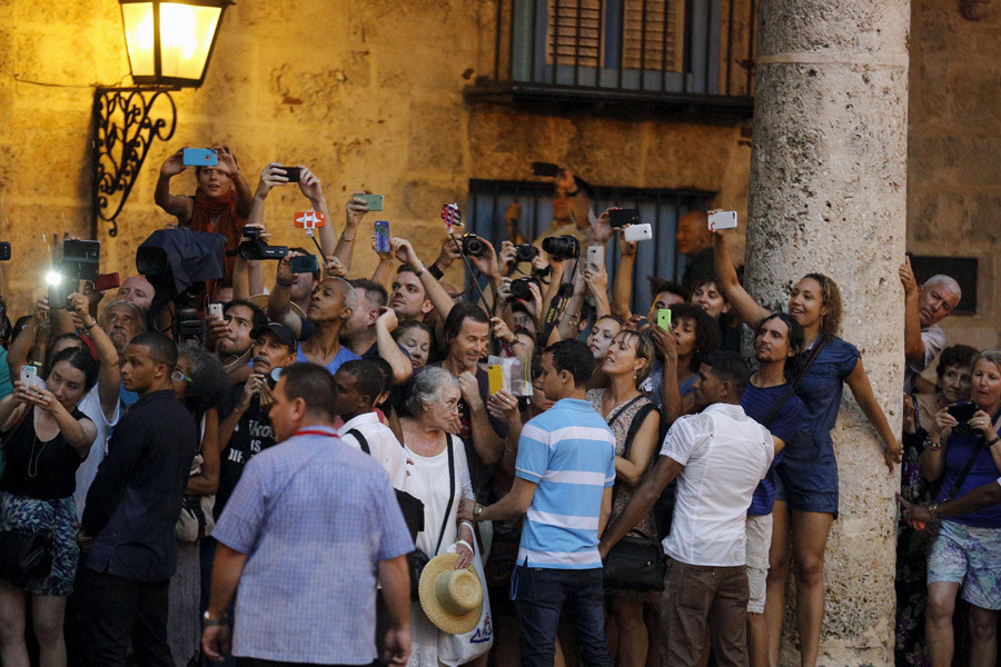 Tourists and local residents take pictures as U.S. President Barack Obama (not pictured) tours Old Havana with his family at the start of a three-day visit to Cuba, in Havana March 20, 2016. © Carlos Barria