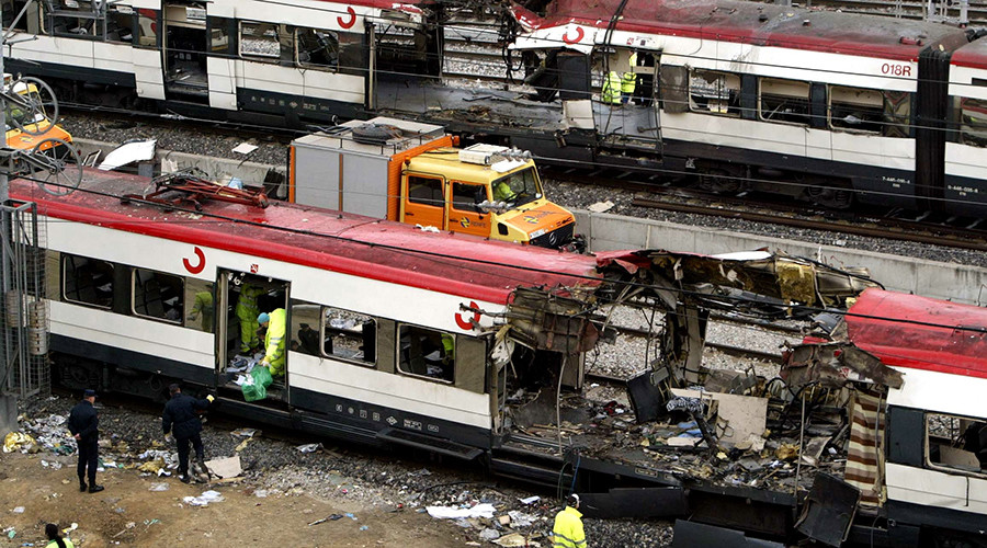 Railway workers remove debris from the wreckage of a bombed public train as a second destroyed train is pulled out of Atocha train station in Madrid in this March 12, 2004 file photo © Stringer