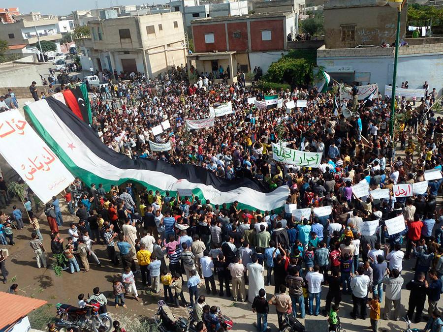 Demonstrators protesting against Syria's President Bashar al-Assad unfurl a giant Syrian flag in Hula, near Homs October 27, 2011 © HO