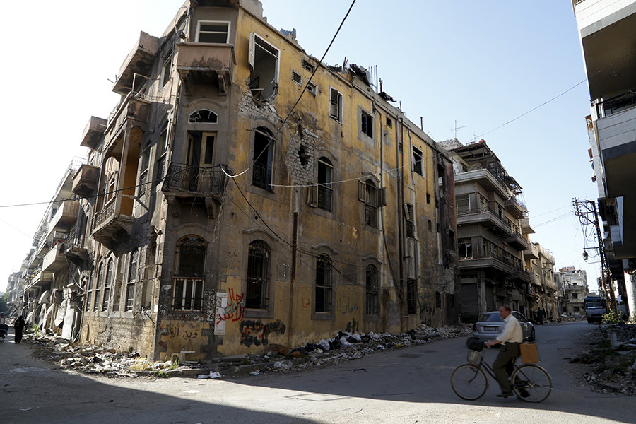 A man rides a bicycle near a building damaged during the Syrian conflict between government forces and rebels in Homs, Syria May 13, 2014 © Omar Sanadiki