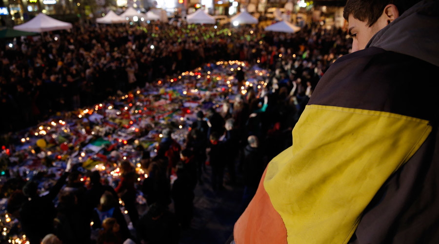 A man is draped with a Belgian flag as people gather at the Place de la Bourse to pay tribute to the victims of bomb attacks in Brussels, Belgium, March 25, 2016. © Christian Hartmann