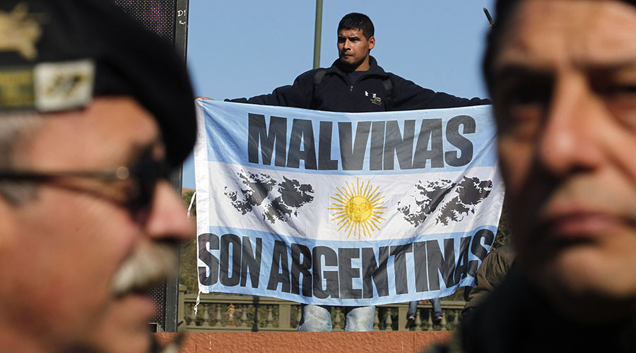 """A man holds a sign which reads,""""Islas Malvinas belongs to Argentina"""". ©Enrique Marcarian"""
