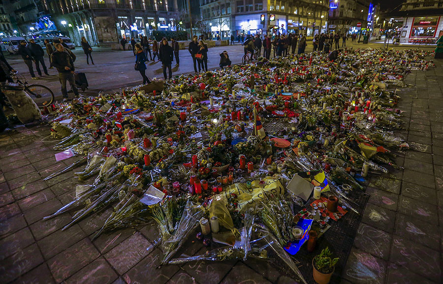People walk past a street memorial for the victims of bomb attacks in Brussels metro and Brussels international airport of Zaventem, in Brussels, Belgium, March 28, 2016. © Yves Herman