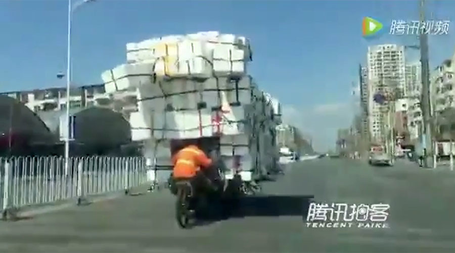 Chinese man defies gravity to transport mountain of boxes on tiny bike (VIDEO)