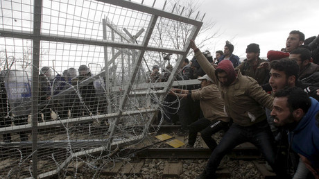 Stranded refugees and migrants try to bring down part of the border fence during a protest at the Greek-Macedonian border, near the Greek village of Idomeni, February 29, 2016. © Alexandros Avramidis