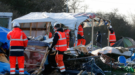 Workmen tear down makeshift shelters in the migrant shanty town called the