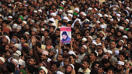 A man holds up the picture of Mumtaz Qadri while attending his funeral prayer at the Liaqat Bagh in Rawalpindi, Pakistan, March 1, 2016. © Faisal Mahmood
