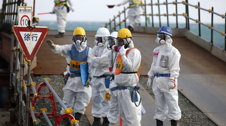 Workers, wearing protective suits and masks, are seen near the No. 3 and No.4 reactor buildings at Tokyo Electric Power Co's (TEPCO) tsunami-crippled Fukushima Daiichi nuclear power plant in Okuma town, Fukushima prefecture, Japan February 10, 2016. © Toru Hanai