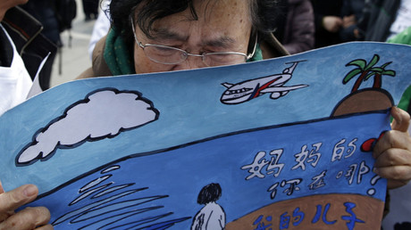 Wang Guohui, mother of a passenger of the missing Malaysia Airlines flight MH370, cries while holding a painting which her family made for wishing the return of her son, at Yonghegong Lama Temple in Beijing March 8, 2015. © Kim Kyung-Hoon