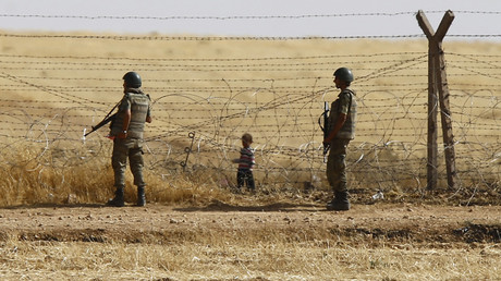 Turkish soldiers stand guard as a Syrian refugee boy waits behind the border fences to cross into Turkey on the Turkish-Syrian border © Osman Orsal
