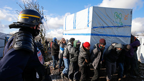Migrants move a makeshift shelter during the dismantlement of the southern part of the shanty town called the