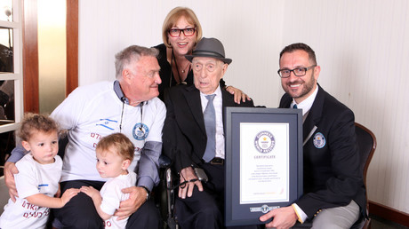 Marco Frigatti (R), Head of Records for Guinness World Records, presenting Israel Kristal (2nd-R) with his certificate of achievement for Oldest living man. © AFP photo / Dvir Rosen / Guinness World Records