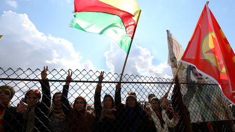 Kurdish people carry flags as they take part in a protest in the city of al-Derbasiyah, on the Syrian-Turkish border © Rodi Said
