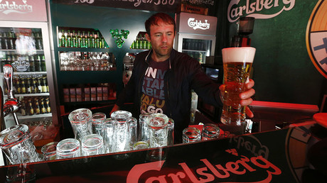 A bartender holds a glass of Carlsberg beer in a bar in St. Petersburg © Alexander Demianchuk