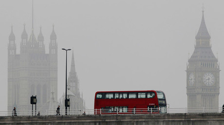 A bus crosses Waterloo bridge in front of the Houses of Parliament during a misty morning in London © Luke MacGregor