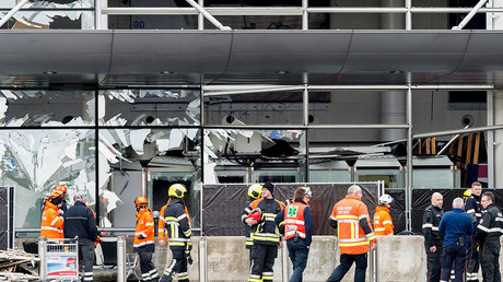 Staff members at Brussels national airport and rescuers stand outside the terminal for a ceremony following bomb attacks in Brussels metro and Belgium's National airport of Zaventem, Belgium, March 23, 2016. ©Geert Vanden Wijngaert