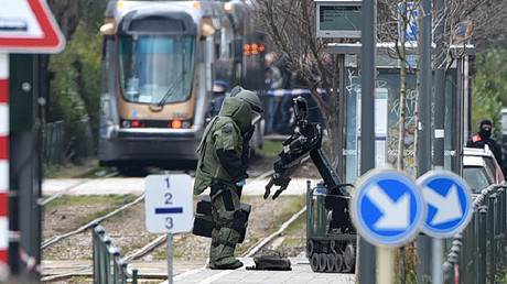 An agent of a bomb squad unit action and a robot stand next to a suspicious object at a tramway station on March 25, 2016 in Schaerbeek suburb, Brussels © Patrik Stollarz