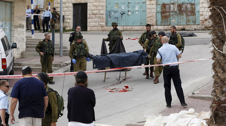 Israeli troops carry the body of a Palestinian who was shot dead after attacking an Israeli soldier. © Mussa Qawasma