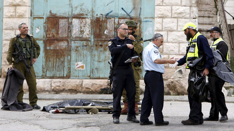 Israeli security forces inspect the scene as the dead body of one of two Palestinians, whom the Israeli military said were shot dead by Israeli troops after they attacked an Israeli soldier, is covered in Tal Rumaida in the West Bank city of Hebron March 24, 2016. © Mussa Qawasma