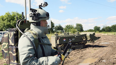 A combat engineer of the Southern Military District's Engineers Corps wears protective gear and holds console for operating the remote-controlled Uran-6 robotic system. ©Said Tsarnaev