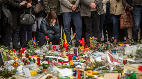 A woman reacts during a minute of silence held at a makeshift memorial in front of Brussel's Stock Exchange on Place de la Bourse (Beursplein) on March 24, 2016, two days after a triple bomb attack. © Philippe Huguen