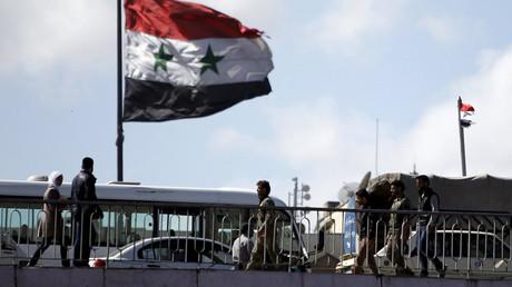 People walk near a Syrian national flag © Omar Sanadiki