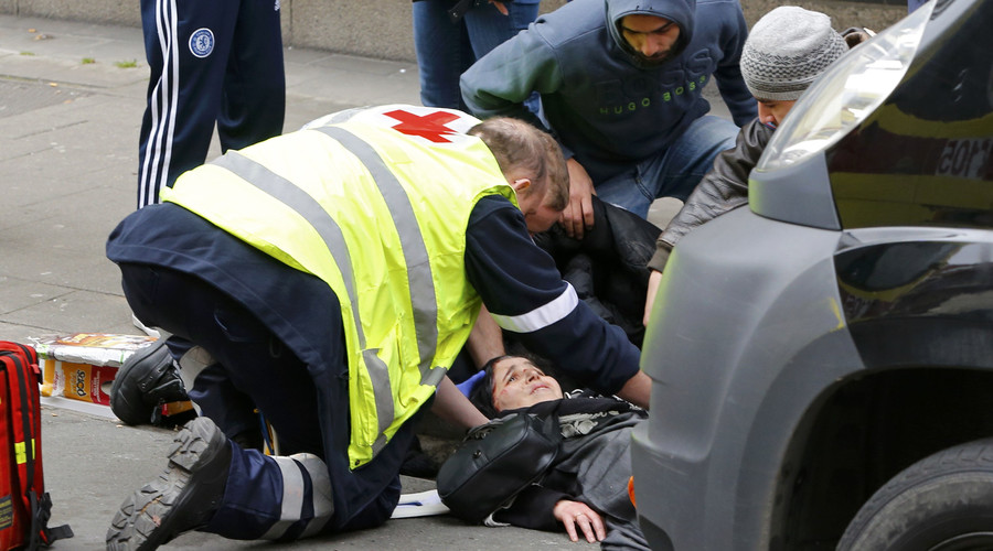 Rescue workers give aid to a woman who was struck by a car that ran through a road block in the Brussels district of Molenbeek, Belgium, April 2, 2016. © Yves Herman