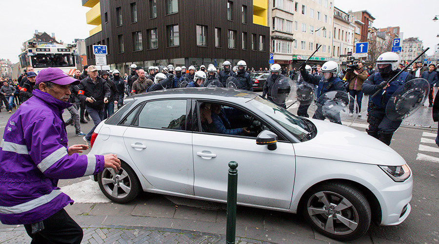 A Belgian police officer points his gun while riot police use their truncheons at a car driving towards a police road block before it hit and injured a woman on the street in the Brussels district of Molenbeek, Belgium, April 2, 2016 © Yves Herman