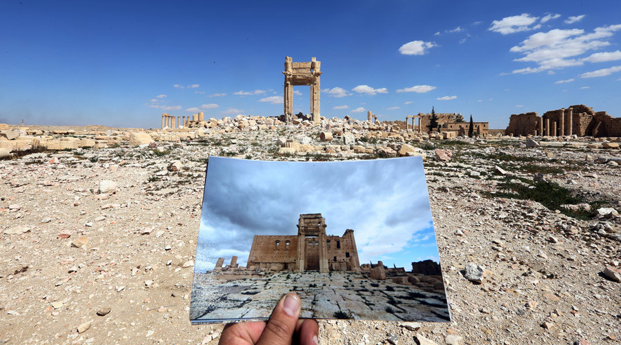 A photographer holding his picture of the Temple of Bel taken on March 14, 2014 in front of the remains of the historic temple after it was destroyed by Islamic State (IS) group jihadists in September 2015 in the ancient Syrian city of Palmyra.© Joseph Eid