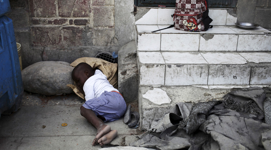 A boy takes a nap on a street in Port-au-Prince, Haiti. © Andres Martinez Casares