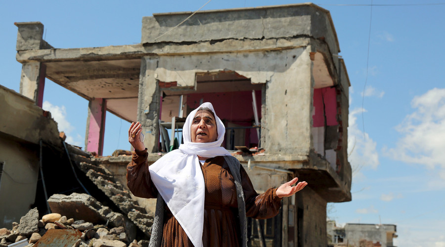 A woman reacts as she stands in front of her house, which was damaged during the security operations and clashes between Turkish security forces and Kurdish militants, in the southeastern town of Idil, Turkey, March 31, 2016. © Sertac Kayar