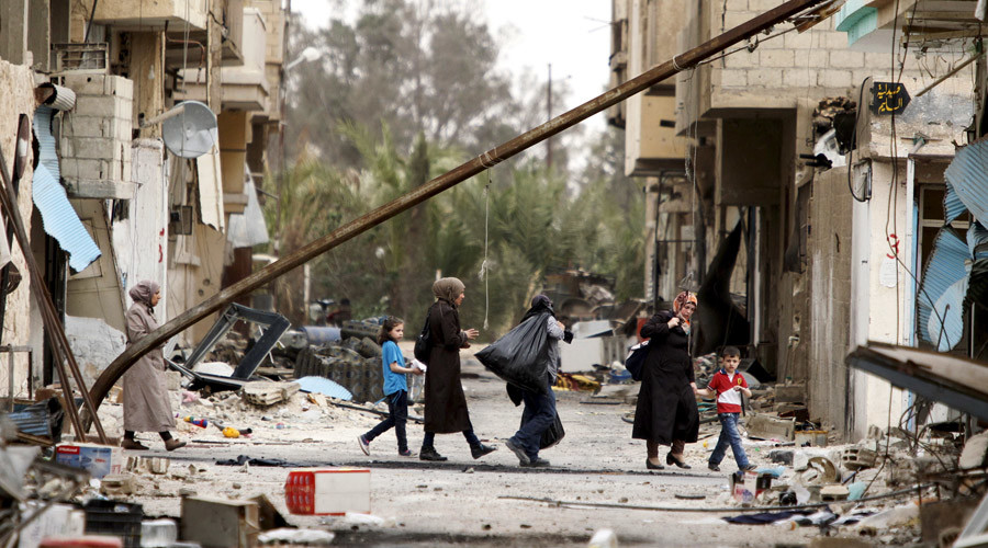 Residents carry belongings they collected from their damaged homes as they walk during a return visit to the city of Palmyra, Syria April 9, 2016. © Omar Sanadiki