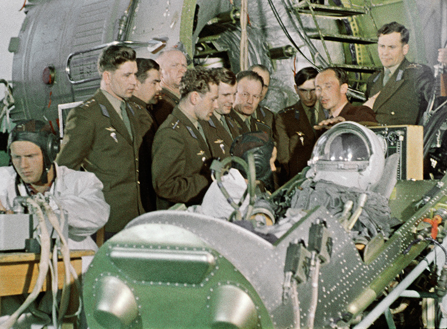 Pilots German Titov (centre left) and Yuri Gagarin (centre 2nd left) with the cosmonaut training group study the space equipment © RIA Novosti