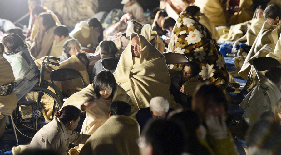 Local residents wrap themselves in blankets as they sit on the road in front of the town office building after an earthquake in Mashiki town, Kumamoto prefecture, southern Japan, in this photo taken by Kyodo April 15, 2016. © Kyodo