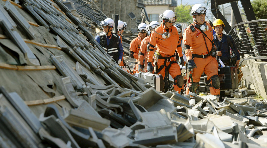 Firefighters walk among collapsed houses caused by an earthquake in Mashiki town, Kumamoto prefecture, southern Japan, in this photo taken by Kyodo April 15, 2016. © Kyodo