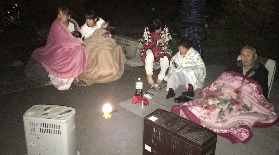 Local residents wrap themselves in blankets as they sit on the road after they are evacuated from their home after an earthquake in Mashiki town, Kumamoto prefecture, southern Japan, in this photo taken by Kyodo April 15, 2016. © Kyodo