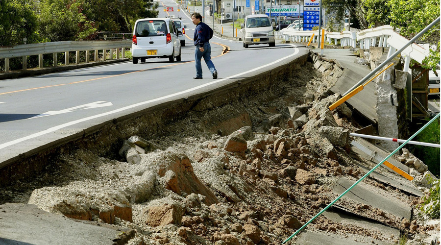 A man walks near a damaged road caused by an earthquake in Mashiki town, Kumamoto prefecture, southern Japan, in this photo taken by Kyodo April 15, 2016. © Kyodo