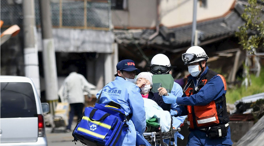 An injured person is carried by rescuers near a damaged house caused by an earthquake in Mashiki town, Kumamoto prefecture, southern Japan, in this photo taken by Kyodo April 15, 2016. © Kyodo