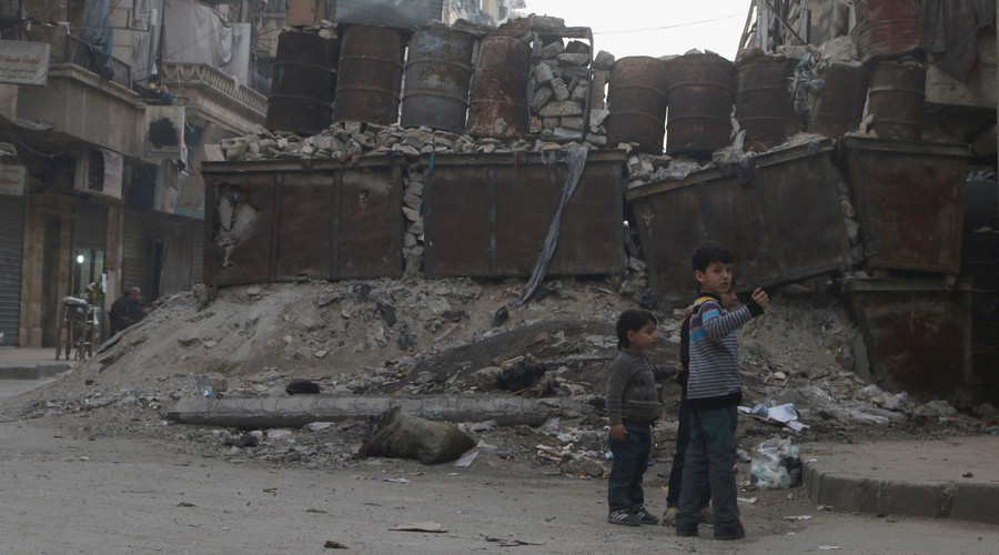 Children play near barricades in a street in Aleppo, Syria