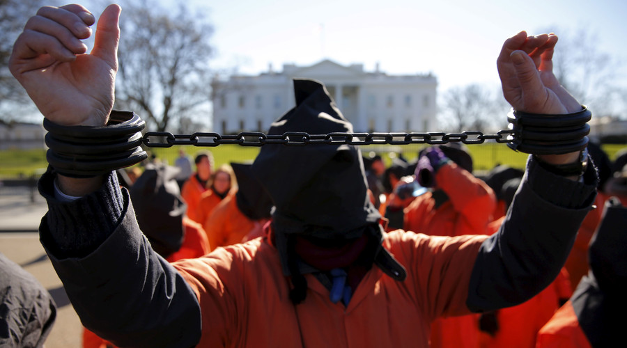 Protesters in orange jumpsuits, including one in plastic shackles, from organizations including Amnesty International USA rally outside the White House to demand the closure of the U.S. prison at Guantanamo Bay, in Washington. © Jonathan Ernst