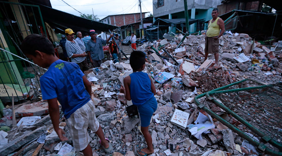 People stand amongst the rubble of fallen homes in Manta on April 17, 2016, after a powerful 7.8-magnitude earthquake struck Ecuador on April 16. © Juan Cevallos