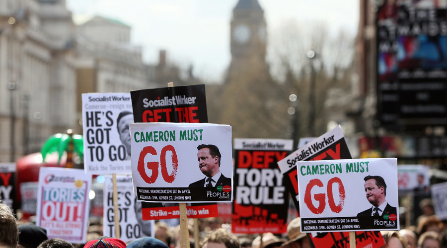 Demonstrators hold placards during a protest outside Downing Street in Whitehall, central London, Britain April 9, 2016. © Neil Hall