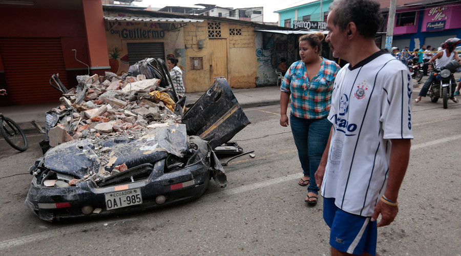 People walk past a car squashed by rubble after a 7.8-magnitude quake in Portoviejo, Ecuador on April 17, 2016. © Juan Cevallos