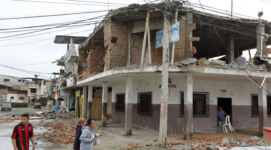 People walk by damaged buildings after an earthquake struck off Ecuador's Pacific coast, at Tarqui neighborhood in Manta April 17, 2016. © Guillermo Granja