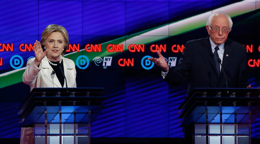 Democratic U.S. presidential candidate Hillary Clinton (L) speaks as Senator Bernie Sanders reacts during a Democratic debate hosted by CNN and New York One at the Brooklyn Navy Yard in New York April 14, 2016. © Lucas Jackson