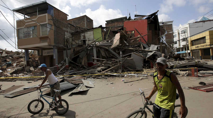 Residents hold their bicycles as damaged and collapsed buildings are seen in the background after an earthquake struck off the Pacific coast, in Portoviejo, Ecuador, April 18, 2016. © Henry Romero